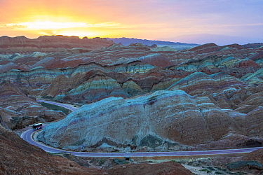Tourist bus on winding road through Rainbow Mountains, eroded hills of sedimentary conglomerate and sandstone. At sunrise, Zhangye National Geopark, China Danxia UNESCO World Heritage Site, Gansu Prov...