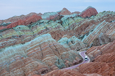 Tourist bus on winding road through eroded hills of sedimentary conglomerate and sandstone. Rainbow Mountains, Zhangye National Geopark, China Danxia UNESCO World Heritage Site, Gansu Province, China....