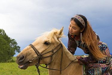 Mongol woman in traditional dress riding horse, portrait. Bashang Grassland, near Zhangjiakou, Hebei Province, Inner Mongolia, China. June 2018.