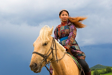 Mongol woman in traditional dress riding horse, portrait. Bashang Grassland, near Zhangjiakou, Hebei Province, Inner Mongolia, China. 2018.