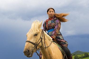 Mongol woman in traditional dress riding horse, portrait. Bashang Grassland, near Zhangjiakou, Hebei Province, Inner Mongolia, China. 2018.