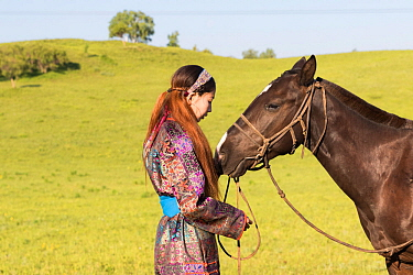 Mongol woman in traditional dress with horse, portrait. Bashang Grassland, near Zhangjiakou, Hebei Province, Inner Mongolia, China. July 2018.