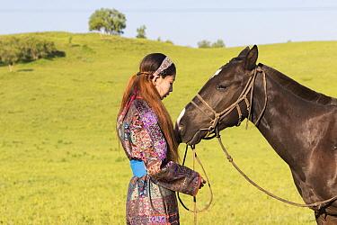 Mongol woman in traditional dress with horse, portrait. Bashang Grassland, near Zhangjiakou, Hebei Province, Inner Mongolia, China. July 2018.