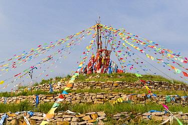 Religious monument with Tibetan prayer flags. Bashang Grassland, near Zhangjiakou, Hebei Province, Inner Mongolia, China. 2018.,