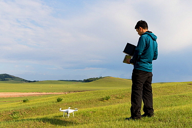Landscape photographer operating drone in Bashang Grassland. Near Zhangjiakou, Hebei Province, Inner Mongolia, China. 2018.