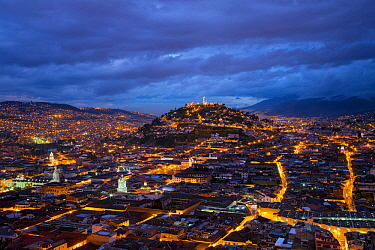 View from San Juan over Quito illuminated at dusk looking twoards Panecillo Hill, Quito, Ecuador, August 2010.