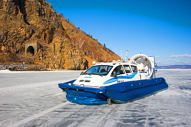 Airboat on lake ice, with tunnel of the Circum-Baikal Railway in background, Lake Baikal, Siberia, Russia. April.