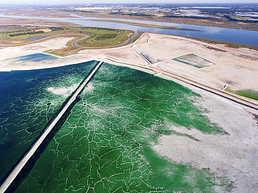 Service road crossing an abandoned pond used for the disposal and stacking of phosphogypsum with crystallised patterns and shallow, but highly toxic radioactive green water in Huelva, Southern Spain....