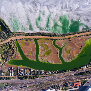 Coloured water leaking from photogypsum storage pond creates tidal channels in saltmarsh habitat. Huelva, Southern Spain. Railway lines pass nearby. Phosphogypsum is a radioactive by-product in the ma...