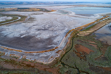 Crystallised patterns in an abandoned pond used for the disposal and stacking of phosphogypsum. Huelva, Southern Spain. Saltmarshes of the RioTinto estuary surround the pond.