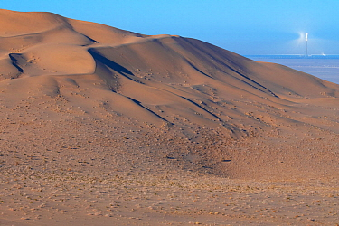 Drifting sand dunes with solar power station in the background, Gobi desert near Dunhuang, Gansu, China.