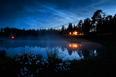 Noctilucent or night shining clouds in sky on a midsummer night, above a pond / lake with cabin and bonfire along the edge. Valgamaa county, Southern Estonia. June 2019.