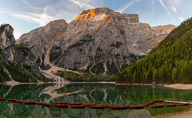 Rental rowboats tied together and first light on Croda del Becco mountain. Lago di Braies, Dolomites, Italy, October 2019.