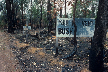 Fire prevention sign 'TAKE CARE, PREVENT BUSHFIRES' burnt in a prescribed burn. Darling Range, Western Australia. October 1999.