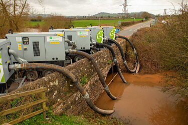 Environment Agency pumping floodwater from the River Lugg, Mordiford to protect the medieval bridge during the floods caused by Storm Dennis, Herefordshire, England, UK. February 2020.