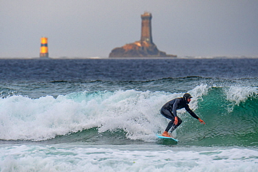 Lighthouse La Vieille and surfer in wetsuit riding a wave on surfboard at the Pointe du Raz, Finist�re, Brittany, France, September 2019