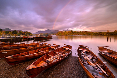 Rowing boats and jetties along the shore of Derwentwater, morning light and rainbow, Keswick, Cumbria, The Lake District, UK. October 2019.