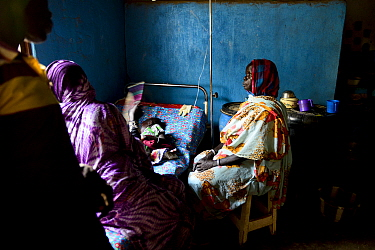 Girl rests while being treated for malaria in the small rural hospital in Moukoulou, southern Chad. Her family watches over her. Malaria disease is very common in this part of the country in the rainy...