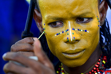 Man from Wodaabe nomadic tribe painting face for Gerewol celebration, a gathering of different clans in which women choose a husband. Men dress in best clothes and ornaments and sing and parade in fro...