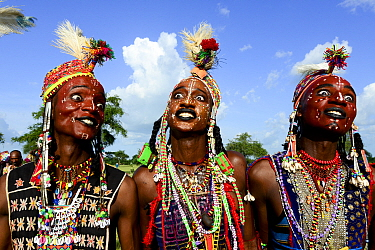 Three men from Wodaabe nomadic tribe celebrating Gerewol, a gathering of different clans in which women choose a husband. Men dress in best clothes and ornaments to sing and dance in front of the youn...