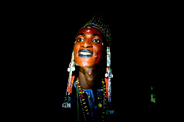 Man from Wodaabe ethnic group,head portrait at night. During Gerewol gathering of different clans women choose a husband. Men dress in best clothes and ornaments and sing and parade in front of the yo...