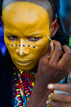 Man from Wodaabe ethnic group painting face for Gerewol celebration, a gathering of different clans in which women choose a husband. Men dress in best clothes and ornaments and sing and parade in fron...