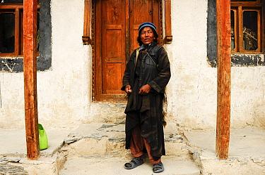 Ladakhi woman standing on steps of small monastery. At 3900m altitude. Honupatta, Ladakh, India. 2011.