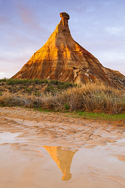 Castildetierra mountain rock formation, reflected in river in morning light. Bardenas Reales Natural Park. Navarre. Spain. November 2013.