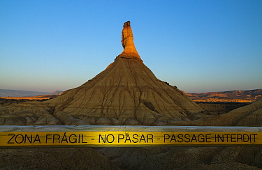 Barrier in front of Castildetierra mountain to protect rock formation from erosion, in morning light. Bardenas Reales Natural Park. Navarre, Spain. February 2018.