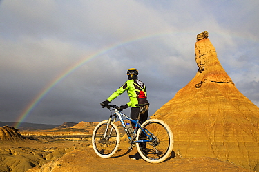 Cyclist beside Castildetierra mountain looking at rainbow over badlands of Bardenas Reales Natural Park. Navarre, Spain. February 2015.