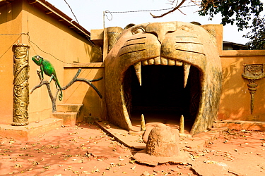 Great voodoo temple, cat or tiger sculpture surrounding an entrance with a chameleon mural on wall. Abomey, Benin, 2020.