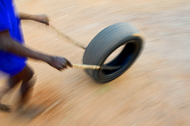 Somba boy playing, rolling a car tyre. Benin, 2020.