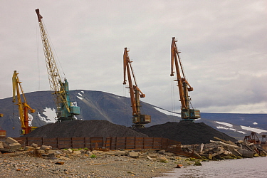 Large piles of coal and coal ash lie on the ground at the Port of Provideniya, very close to the water's edge, at the shore of Komsoloskaya Bay , Bering Sea, Russia.