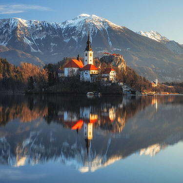 Church of the Assumption and mountains reflected in Lake Bled. Upper Carniola, Slovenia. February 2020.