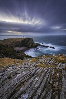 View across rocky cliffs to Stoer Lighthouse. Assynt, Sutherland, Highland, Scotland, UK. January