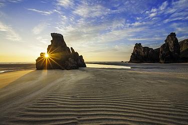 Sun rays over rock formation on Port Geiraha beach. New Tolsta, Isle of Lewis, Scotland, UK. June 2010.