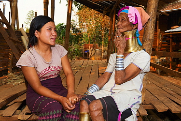 Generation gap - Kayan Lahwi woman with brass neck coils and traditional clothing chatting with her grand daughter, who is not wearing any coils and dressed in a modern style. The Long Neck Kayan (als...
