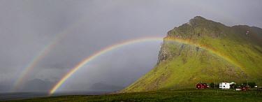 Double rainbow over coast, houses at end of rainbow. Myrland, Flakstadoya, Lofoten, Norway. June 2017.