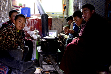 Group of novice monks sitting around stove whilst resting at Bangpu Monastery / Panphuk Gompa, Sangdui, Sichuan, China. 2016.