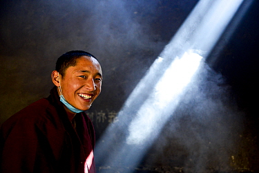 Buddhist monk with face mask round neck in steamy kitchen of Palpung Monastery, portrait. Palpung Monastery, Kham, Dege County, Garze Tibetan Autonomous Prefecture, Sichuan, China. 2016.