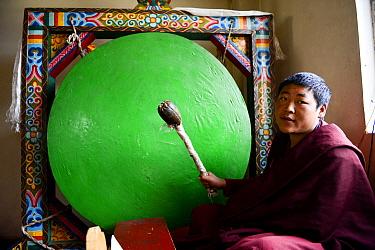 Monk beating gong during Buddhist mass. Palpung Monastery, Kham, Dege County, Garze Tibetan Autonomous Prefecture, Sichuan, China. 2016.