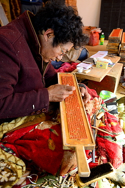 Craftsman creating wooden plate for printing Buddhist prayers. Palpung Monastery, Kham, Dege County, Garze Tibetan Autonomous Prefecture, Sichuan, China. 2016.