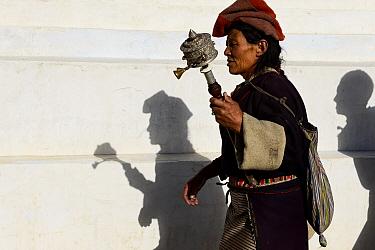Tibetan Buddhist pilgrim holding prayer wheel, walking, Ganden Thubchen Choekhorling Monastery, shadows on wall. Litang, Garze Tibetan Autonomous Prefecture, Sichuan, China. 2016.