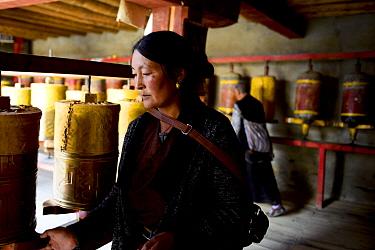 Tibetan Buddhist pilgrim turning prayer wheels, praying. Ganden Thubchen Choekhorling Monastery. Litang, Garze Tibetan Autonomous Prefecture, Sichuan, China. 2016.