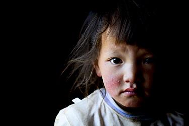 Child on Buddhist pilgrimage, portrait. Ganden Thubchen Choekhorling Monastery. Litang, Garze Tibetan Autonomous Prefecture, Sichuan, China. 2016.