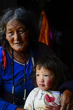 Portrait of woman and child, Tibetan Buddhist pilgrims at Ganden Thubchen Choekhorling Monastery. Litang, Garze Tibetan Autonomous Prefecture, Sichuan, China. 2016.