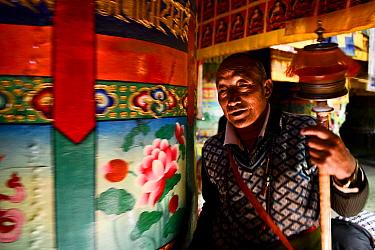 Tibetan Buddhist pilgrim praying at Ganden Thubchen Choekhorling Monastery. Litang, Garze Tibetan Autonomous Prefecture, Sichuan, China. 2016.