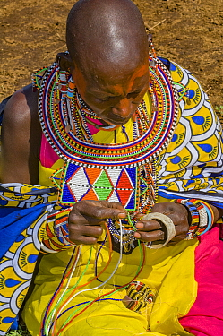 Maasai woman creating traditional bead jewellery. Maasai Mara National Reserve, Kenya. 2007.