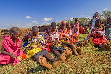 Maasai women creating traditional bead jewellery, children watching. Maasai Mara National Reserve, Kenya. 2007.