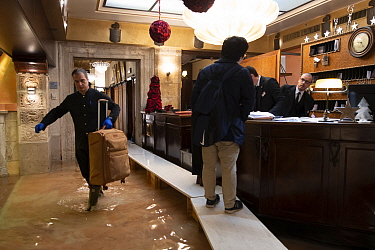 Tourist checking into hotel during flooding in Venice, Italy, December 2019.